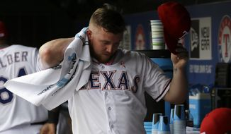 Texas Rangers' Robbie Ross prepares to walk onto the field before a baseball game against the Boston Red Sox, Sunday, May 11, 2014, in Arlington, Texas. (AP Photo/Tony Gutierrez)