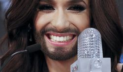 Singer Conchita Wurst representing Austria who performed the song 'Rise Like a Phoenix' smile as she sits by the trophy during a press conference after winning the Eurovision Song Contest  in the B&W Halls in Copenhagen, Denmark, Saturday, May 10, 2014.(AP Photo/Frank Augstein)
