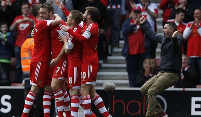 Southampton's Rickie Lambert, second left, celebrates his goal against Manchester United with teammates as a supporter, right, runs onto the pitch to join them during their English Premier League soccer match at St Mary's stadium, Southampton, England, Sunday, May 11, 2014. (AP Photo/Sang Tan)