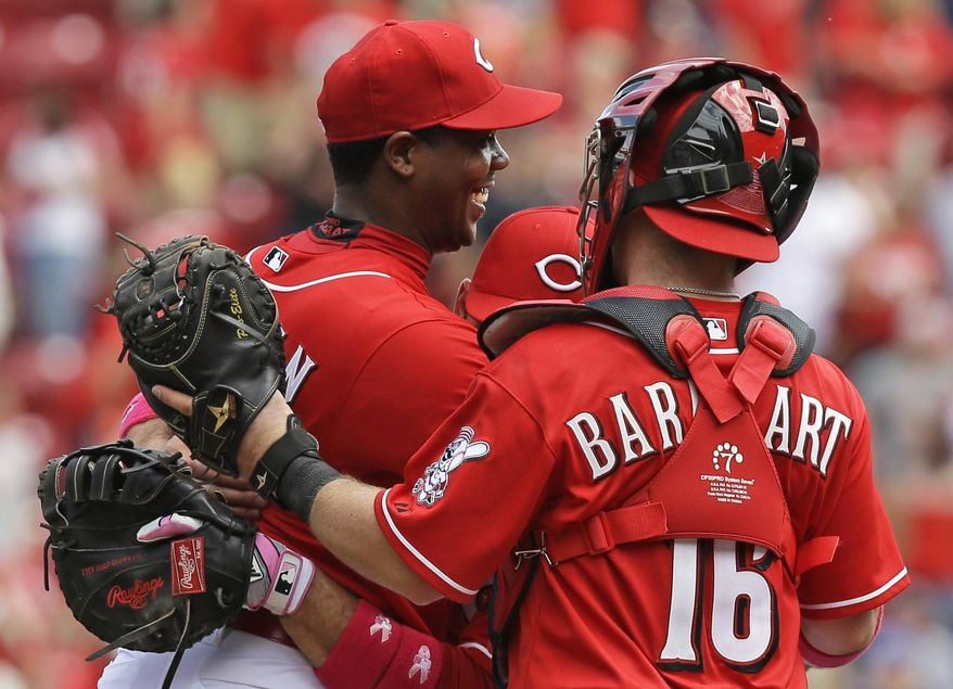 Cincinnati Reds relief pitcher Aroldis Chapman, left, is hugged by Joey Votto and Tucker Barnhart (16) after Chapman earned his first save of the season in the Reds 4-1 win over the Colorado Rockies in a baseball game, Sunday, May 11, 2014, in Cincinnati. Chapman was making his first appearance since being hit in the head with a line drive in spring training. (AP Photo/Al Behrman)