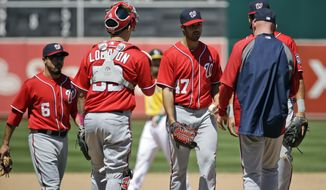 Washington Nationals starting pitcher Gio Gonzalez, center, is pulled from a baseball game during the fifth inning against the Oakland Athletics, Sunday, May 11, 2014, in Oakland, Calif. (AP Photo/Marcio Jose Sanchez)