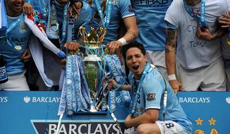 Manchester City's Samir Nasri, front, holds the cup and celebrates with team mates after being crowned Champions after the English Premier League soccer match between Manchester City and West Ham United at the Etihad Stadium,  Manchester, England, Sunday, May 11, 2014. (AP Photo/Rui Vieira)