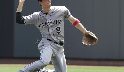 Colorado Rockies second baseman DJ LeMahieu throws to first for the out after fielding a ground ball hit by Cincinnati Reds' Joey Votto in the fourth inning of a baseball game, Sunday, May 11, 2014, in Cincinnati. (AP Photo/Al Behrman)
