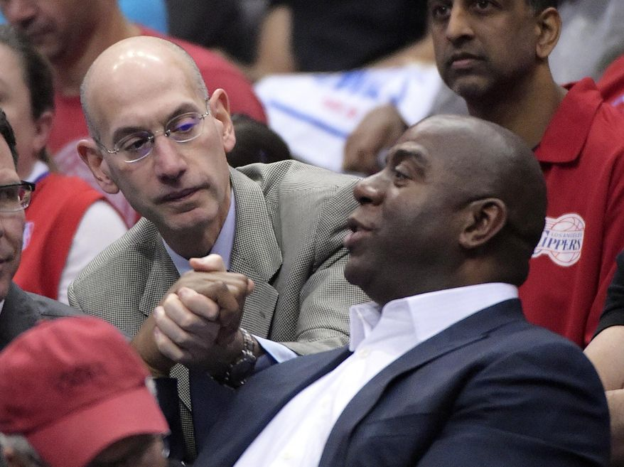 NBA Commissioner Adam Silver, left, shakes hands with Magic Johnson as they watch the Los Angeles Clippers play the Oklahoma City Thunder in the first half of Game 4 of the Western Conference semifinal NBA basketball playoff series, Sunday, May 11, 2014, in Los Angeles. (AP Photo/Mark J. Terrill)
