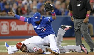 Toronto Blue Jays third baseman Juan Francisco, top, falls on Los Angeles Angels' Howie Kendrick who slid safely into third on an error during fourth-inning baseball game action in Toronto, Sunday, May 11, 2014. (AP Photo/The Canadian Press, Frank Gunn)