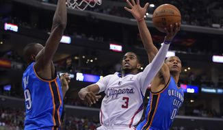 Los Angeles Clippers guard Chris Paul, center, puts up a shot between Oklahoma City Thunder defenders Serge Ibaka, left, of Congo, and Russell Westbrook in the first half of Game 4 of the Western Conference semifinal NBA basketball playoff series, Sunday, May 11, 2014, in Los Angeles. (AP Photo/Mark J. Terrill)