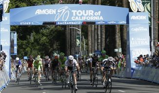 Mark Cavendish, center, of Great Britain, riding for the Omega Pharma-Quickstep Cycling Team, pulls up after crossing the finish line ahead of second place finisher John Degenkolb, right, of Germany, riding for  Team Giant-Shimano right, to win the Stage I of Tour of California cycling in Sacramento, Calif., Sunday, May 11, 2014.  In a nearly photo-finish Cavendish completed the 120 mile stage in 4 hours, 47 minutes, 17 seconds to earn the overall race leader's yellow jersey. (AP Photo/Rich Pedroncelli)