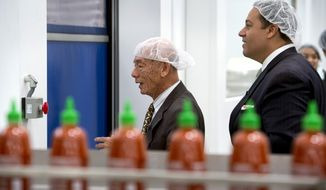 Texas State Representative Jason Villalba, right, of Dallas, Texas, tours the Huy Fong Foods, Inc. manufacturing plant, maker of Sriracha hot sauce, with founder and CEO David Tran, in Irwindale, Calif. May 12, 2014.  Texas officials are trying to convince the Sriracha maker to move to their state after the city of Irwindale declared them a public nuisance. (AP Photo/San Gabriel Valley Tribune,  Leo Jarzomb)