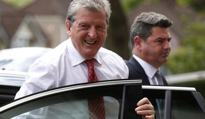 England's soccer manager Roy Hodgson, left, arrives to announce the national squad for the upcoming World Cup in Brazil, in Luton, England, Monday, May 12, 2014.(AP Photo/Sang Tan)