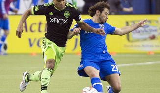 FILE- In this March 23, 2014, file photo, Montreal Impact's Hernan Bernardello, right, challenges Seattle Sounders' DeAndre Yedlin for the ball during the first half of an MLS soccer game in Montreal. Clint Dempsey is a given. Brad Evans seems likely to get an invite. DeAndre Yedlin may get his shot to prove worthy of a World Cup roster spot. Three of the Seattle Sounders' top players could be invited to World Cup training camp for the U.S. team next week. (AP Photo/The Canadian Press, Graham Hughes, File)