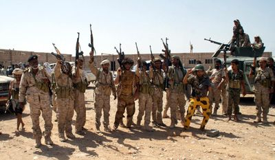 In this photo provided by Yemen's Defense Ministry, Yemen's army soldiers hold up their weapons at an area seized from al-Qaida in the southeastern province of Shabwa, Yemen, Thursday, May 8, 2014. Yemeni armed forces on Thursday swept al-Qaida fighters out of a district in the country's south, one of the main goals of the major offensive waged by the military the past two weeks, the Defense Ministry said, amid fears of retaliatory attacks which officials say prompted the closure of the U.S. Embassy in the capital as a precaution. (AP Photo/Yemen's Defense Ministry)