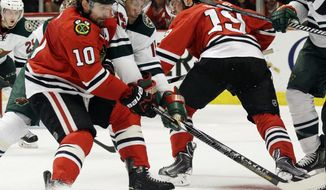 Chicago Blackhawks' Patrick Sharp (10) and Minnesota Wild's Dany Heatley, second from left, battle for the puck during the second period in Game 5 of an NHL hockey second-round playoff series in Chicago, Sunday, May 11, 2014. The Blackhawks won 2-1. (AP Photo/Nam Y. Huh)