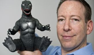 In this Wednesday, April 23, 2014 photo, entertainment and intellectual property litigation attorney Aaron Moss of Greenberg Glusker shows a licensed, original Godzilla Imperial product at his Century City office in Los Angeles. He spews radioactive fire, razes cities and pummels creatures from Earth and beyond, but even Godzilla sometimes needs a good lawyer. (AP Photo/Damian Dovarganes)
