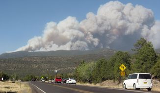 This Sunday May 11, 2014 photo shows plumes of smoke from a wildfire as cars drive on NM 15 in Pinos Altos, N.M. (AP Photo/Silver City Daily Press & Independent, Roger Lanse)