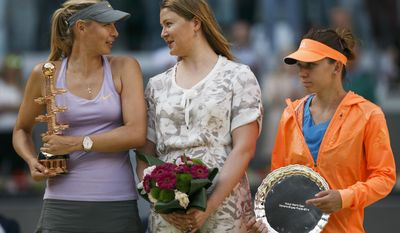 Maria Sharapova from Russia, left, celebrates her victory holding her trophy as she talks to former tennis player Dinara Safina, center, and Simona Halep from Romania, right, after a Madrid Open tennis tournament final match in Madrid, Spain, Sunday, May 11, 2014. (AP Photo/Andres Kudacki)