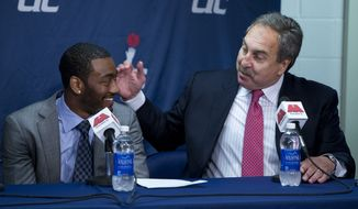 Washington Wizards general manager Ernie Grunfeld, right, congratulates Wizards point guard John Wall during a news conference to announce Wall's new contract with the NBA basketball team at the Verizon Center on Thursday, Aug. 1, 2013, in Washington. Wall signed a five-year, $80 million extension to remain with the team. (AP Photo/Evan Vucci)