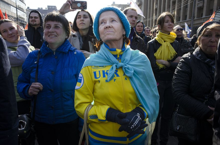 A woman wearing clothes in the color of the Ukrainian flag listens to a speaker during a rally against pro-Putin media in Moscow, Russia, Sunday, April 13, 2014. More than 10,000 people have turned out in Moscow for an anti-Kremlin rally to denounce Russian state television's news coverage, particularly of the crisis in neighboring Ukraine. (AP Photo/Alexander Zemlianichenko)