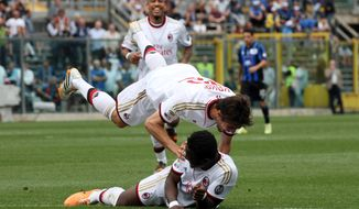 AC Milan's Brazilian Kaka', top, celebrates with teammate Sulley Muntari, of Ghana, after Atalanta's Giampaolo Bellini scored an own goal during a Serie A soccer match in Bergamo, Italy, Sunday, May 11, 2014. (AP Photo/Felice Calabro')