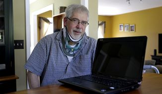 This photo taken May 8, 2014 shows Mark Matulaitis posing with his laptop that he uses for virtual house calls with his neurologist in his home in Salisbury, Md. Matulaitis has had Parkinson's disease since 2011 and sees a neurologist at the University of Rochester via his laptop and special Skype-like software.  (AP Photo/Patrick Semansky)