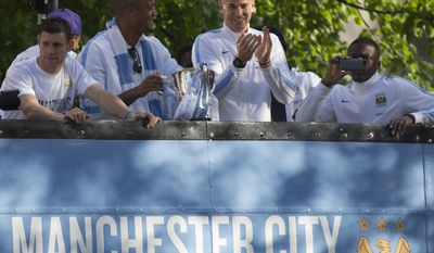 Manchester City's Joe Hart, centre, applauds supporters as he stands with captain Vincent Kompany, centre left, as the team celebrate in the city centre the day after they won the English Premier League title, in Manchester, England, Monday May 12, 2014. (AP Photo/Jon Super)