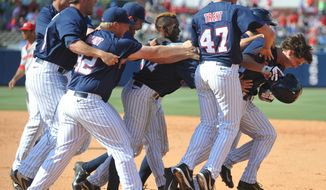 Mississippi's Auston Bousfield, right, is mobbed by his temmates following his game winning single in the 10th inning against Georgia at Oxford-University Stadium in Oxford, Miss. on Sunday, May 11, 2014. Mississippi won 2-1 in 10 innings. (AP Photo/Oxford Eagle, Bruce Newman)