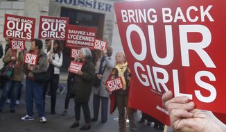 A woman holds a sign during a rally near the Nigerian embassy to raise to show support for the release of the kidnapped girls in Nigeria in Paris, Monday, May 12, 2014. A French official says Nigerian President Goodluck Jonathan has agreed to attend a security summit on Saturday in Paris to focus on the Boko Haram terrorist network, which abducted more than 300 schoolgirls in Nigeria last month. Signs center and left read, save the Nigerian schoolgirls. (AP Photo/Michel Euler)