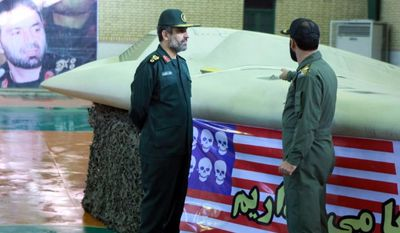 ** FILE ** This photo released Dec. 8, 2011, by the Iranian Revolutionary Guards claims to show Gen. Amir Ali Hajizadeh (left), the chief of the aerospace division of Iran's Revolutionary Guards, listening to an unidentified colonel as he points to a U.S. RQ-170 Sentinel drone that Tehran said its forces downed earlier in the week. (Associated Press/Sepahnews)