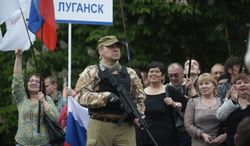 """A gunman stands guard as pro-Russian protesters listen to a speaker as they declare independence for the Luhansk region in eastern Ukraine on Monday, May 12, 2014. The words on the nameplate read """"Luhansk"""". Pro-Russia separatists in eastern Ukraine declared independence Monday for the Donetsk and Luhansk regions following their contentious referendum ballot. (AP Photo/Evgeniy Maloletka)"""
