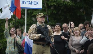 "A gunman stands guard as pro-Russian protesters listen to a speaker as they declare independence for the Luhansk region in eastern Ukraine on Monday, May 12, 2014. The words on the nameplate read ""Luhansk"". Pro-Russia separatists in eastern Ukraine declared independence Monday for the Donetsk and Luhansk regions following their contentious referendum ballot. (AP Photo/Evgeniy Maloletka)"