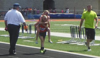 This Saturday, May 10, 2014 photo provided by Ted Crail shows Claire Gruenke, an eighth-grade student at Wesclin Junior High School in Trenton, Ill., carrying her twin sister, Chloe, to the finish line in the 800-meter run at the State Junior High Track Meet in Carterville, Ill. During the 800 meter run, Chloe fell to the ground with a muscle strain and was unable to get back on her feet. So Claire carried her piggyback all the way to the finish line where they both crossed together. (AP Photo/Courtesy of Ted Crail)