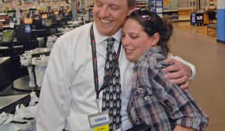 In this photo taken on Monday, May 12, 2014, Wal-Mart store co-manager Derrick Orr, left, and Alesia Madeiros embrace when she stopped by the south Bismarck, N.D., store to shop. The pair first met last Thursday, when Orr delivered Madeiros' baby son in the store parking lot and used his shoe lace to tie off the umbilical cord. (AP Photo/The Bismarck Tribune, Tom Stromme)