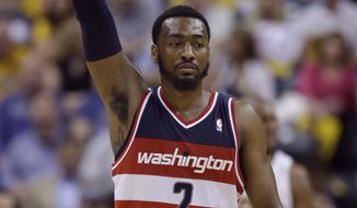 Washington Wizards guard John Wall signals after hitting a three-point basket against the Indiana Pacers during the second half of game 5 of the Eastern Conference semifinal NBA basketball playoff series Tuesday, May 13, 2014, in Indianapolis. (AP Photo/Darron Cummings)