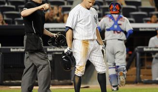Home plate umpire Mike Estabrook holds the ball as New York Yankees' Brett Gardner (11) reacts after striking out off of New York Mets pitcher Jenrry Mejia and leaving a runner on base in the eighth inning of an interleague baseball game at Yankee Stadium on Monday, May 12, 2014, in New York. The Mets won 9-7. (AP Photo/Kathy Kmonicek)