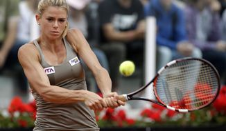 Italy's Camila Giorgi returns the ball to Dominika Cibulkova of Slovakia, at the Italian Open tennis tournament, in Rome, Tuesday, May 13, 2014. (AP Photo/Alessandra Tarantino)