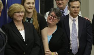 Plantiff's in the federal suit over Virginia's ban on gay marriage, Mary Townley, left, Emily Schall-Townley, second from left,  Carol Schall, center, Tony London, second from right, and Tim Bostic, right, react to comments during a news conference after a hearing on Virginia's same sex-marriage ban in Richmond, Va., Tuesday, May 13, 2014.  The 4th U.S. Circuit Court of Appeals in Richmond heard arguments on a judge's ruling striking down Virginia's same-sex marriage ban.   (AP Photo/Steve Helber)