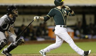 Oakland Athletics' Jed Lowrie swings for a two-run double off Chicago White Sox pitcher Daniel Webb in the seventh inning of a baseball game Monday, May 12, 2014, in Oakland, Calif. (AP Photo/Ben Margot)