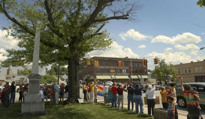 Rally participants wave past cars in Christiansburg, Va., Monday May 12 2014. An assembly of about 50 people waved and held signs in support of marriage equality. The event was part of a series of state-wide organized events.(AP Photo/The Roanoke Times, Matt Gentry)
