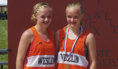 This Saturday, May 10, 2014 photo provided by Ted Crail shows Chloe Gruenke, left, and her twin sister, Claire, both eighth-graders at Wesclin Junior High School in Trenton, Ill., posing for a photo after the State Junior High Track Meet in Carterville, Ill. During the 800-meter run, Chloe fell to the ground with a muscle strain and was unable to get back on her feet. So Claire carried her piggyback all the way to the finish line where they both crossed together. (AP Photo/Courtesy of Ted Crail)
