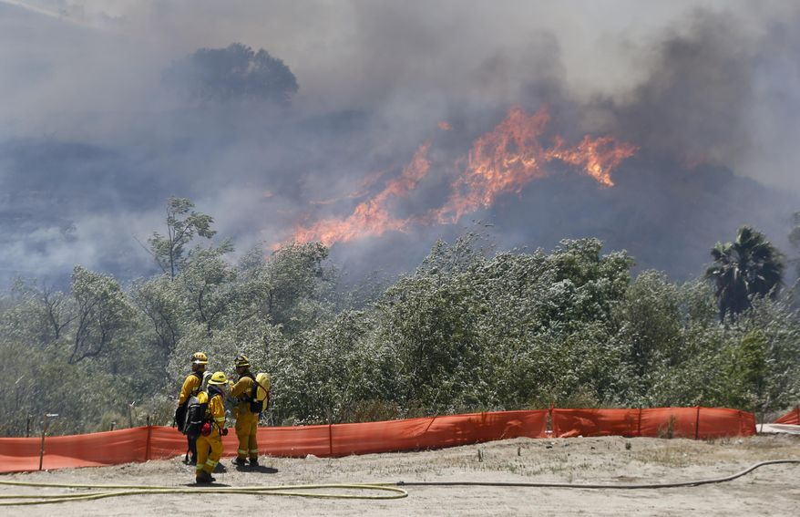 Flames grow as a wild fire burns out-of-control in the north county area of San Diego Tuesday, May 13, 2014, in San Diego.  Wildfires destroyed a home and forced the evacuation of several others Tuesday in California as a high-pressure system brought unseasonable heat and gusty winds to a parched state that should be in the middle of its rainy season. (AP Photo)