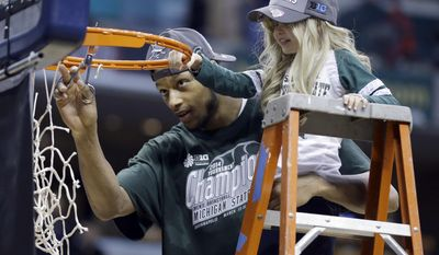 FILE - In this March 16, 2014, file photo, Michigan State forward Adreian Payne, left, cuts the net with Lacey Holsworth, who is battling cancer and has become close to Payne, after Michigan State defeated Michigan 69-55 in an NCAA college basketball game in the championship of the Big Ten Conference tournament in Indianapolis. Dick Vitale Vitale told Lacey Holsworth's father, Matt Holsworth, that he would raise $250,000 in Lacey's name that would be for a pediatric cancer research grant through The V Foundation for Cancer Research. He would do it by the night of his fundraising gala this Friday, May 16, in Sarasota, Florida. (AP Photo/Michael Conroy, File)