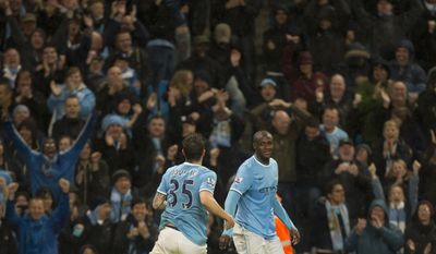 Manchester City's Yaya Toure, right, celebrates with teammate Stevan Jovetic after scoring against Aston Villa during their English Premier League soccer match at the Etihad Stadium, Manchester, England, Wednesday May 7, 2014. (AP Photo/Jon Super)