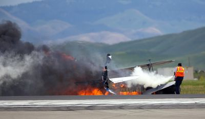 FILE - In this May 4, 2014 file photo, a worker fights a fire after a vintage biplane crashed upside-down on a runway at an air show at Travis Air Force Base in Fairfield, Calif. The pilot, Edward Andreini, 77, of Half Moon Bay, was killed when the plane, flying low over the tarmac, crashed and caught fire. According to a report by the National Transportation Safety Board, released Monday, May 13, 2014, Andreini was making his second attempt at the upside-down stunt 20 feet off the ground when he crashed.(AP Photo/Bryan Stokes, File)
