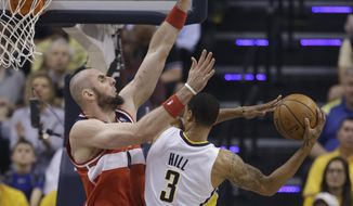 Washington Wizards center Marcin Gortat, left, goes up to block the shot of Indiana Pacers guard George Hill during the first half of game 5 of the Eastern Conference semifinal NBA basketball playoff series Tuesday, May 13, 2014, in Indianapolis. (AP Photo/Darron Cummings)