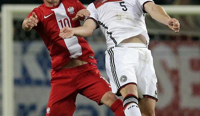 Germany's Shkodran Mustafi, right, and Poland's Ludovic Obraniak, left, challenge for the ball during a friendly soccer match between Germany and Poland in Hamburg, Germany, Tuesday, May 13, 2014.  (AP Photo/Michael Sohn)