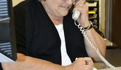 In this April 22, 2014 photo, Becky Bailey answers phones at the Regional Office of Education in Effingham, Ill. Bailey has served the district as an administrative assistant for 50 years. (AP Photo/Effingham Daily News, Bill Grimes)