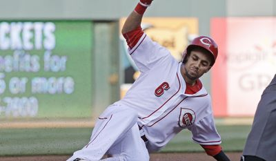 Cincinnati Reds' Billy Hamilton slides into third base with a triple off San Diego Padres starting pitcher Andrew Cashner in the first inning of a baseball game, Tuesday, May 13, 2014, in Cincinnati. (AP Photo)