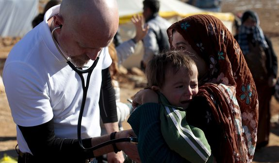 Dr. Batley examines a two year old boy from Al Qusair who has a harsh cough. Tuberculosis is a fear for the Syrian refugees in Arsal do to their unhygienic conditions and lack of aid and medical care. (Credited Image: © Omar Alkalouti)