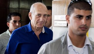 Israel's former Prime Minister Ehud Olmert, center, leaves the Tel Aviv District Court in Israel, Tuesday, May 13, 2014. Olmert was sentenced on Tuesday to six years in prison for his role in wide-ranging bribery case, capping a stunning fall from grace for one of the most powerful men in the country. (AP Photo/Jack Guez, Pool)