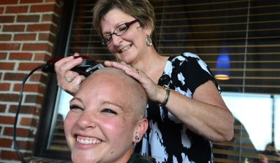 Tiffinie Domer's head is shaved by Pat Whitley as part of the St. Baldrick's Foundation's fundraiser to raise money to help find a cure for childhood cancer on Tuesday, May 13, 2014, at East Coast Wings in Kinston, N.C. (AP Photo/Free Press, Zach Frailey)