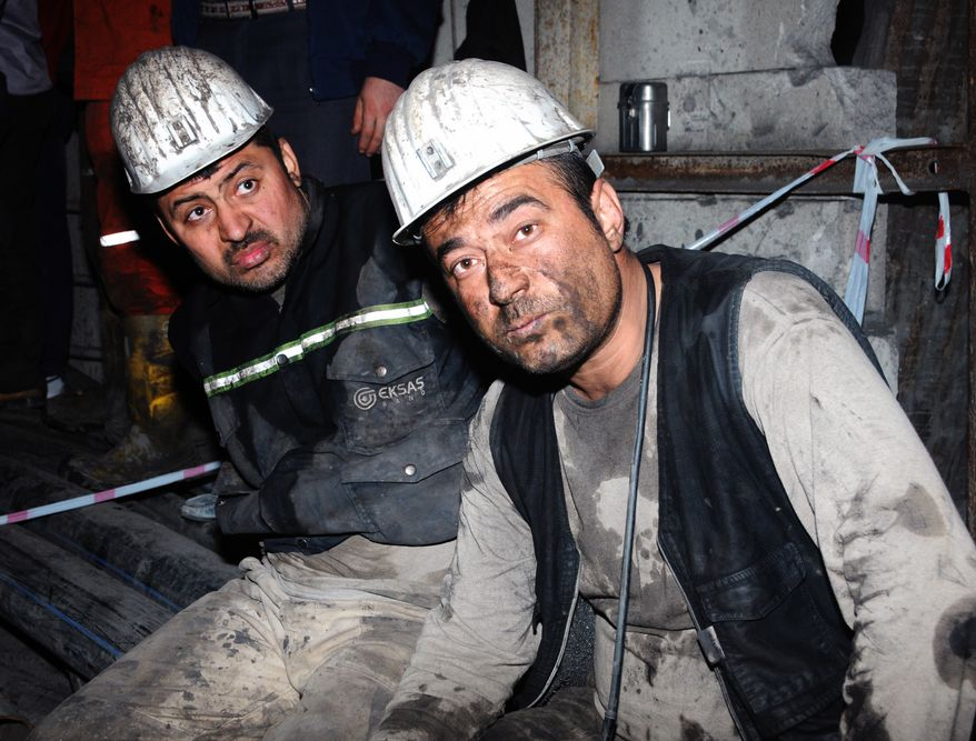 Two miners look around after being rescued hours after an explosion and fire at a coal mine killed at least 17 miners and left up to 300 workers trapped underground, in Soma, in western Turkey, late Tuesday, May 13, 2014, a Turkish official said. The death toll was expected to rise. (AP Photo)